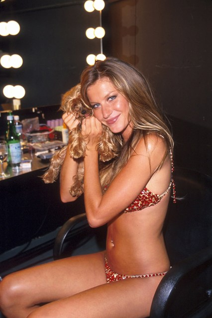 Gisele Bundchen wears the 2000 ruby Fantasy Bra as she poses with her dog backstage.